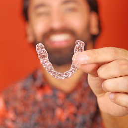 man with a perfect smile holding invisible aligners