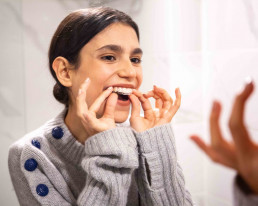 girl putting invisible aligners on